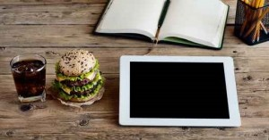 Tablet computer with a hamburger and a glass of cola