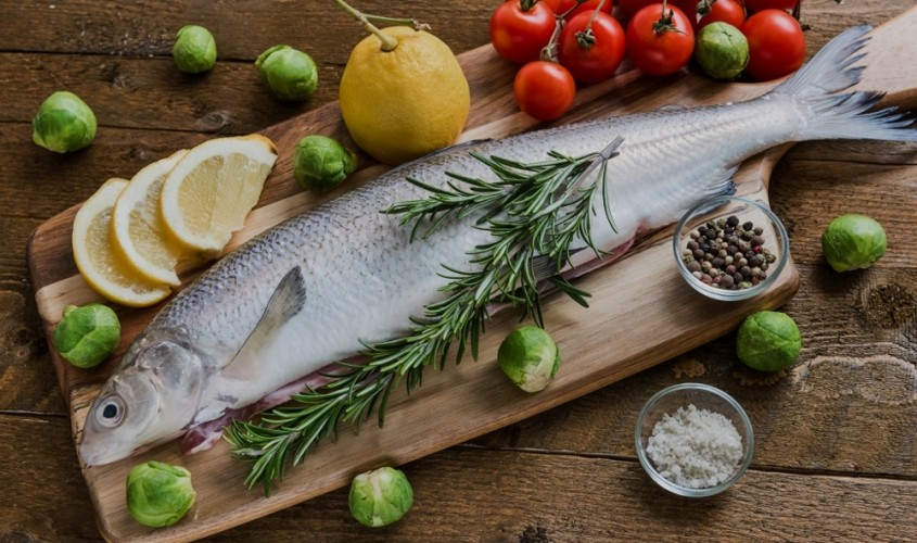 Fresh fish with vegetables on wooden board