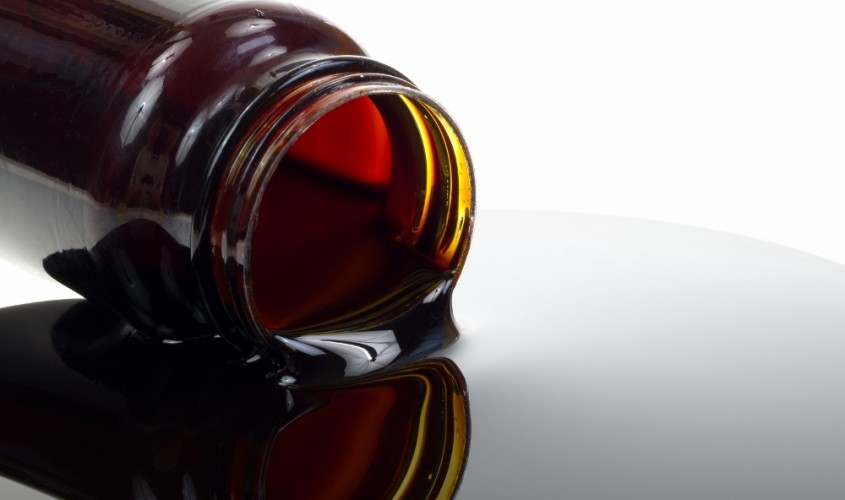 Close view of a jar of spilled molasses syrup