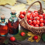 Tincture bottles of hawthorn berries, ripe thorn apples in basket and autumn maple leaves on wooden table. Herbal medicine.