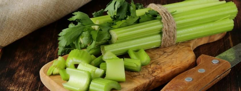chopped green celery on a kitchen wooden board
